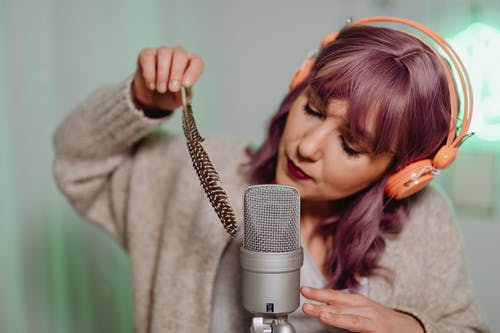 Woman in Gray Sweater Holding Microphone
