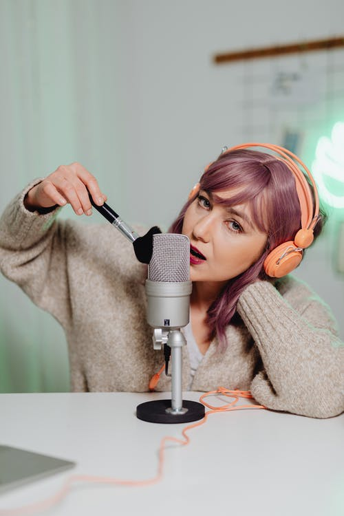A Woman Brushing and Talking on a Microphone
