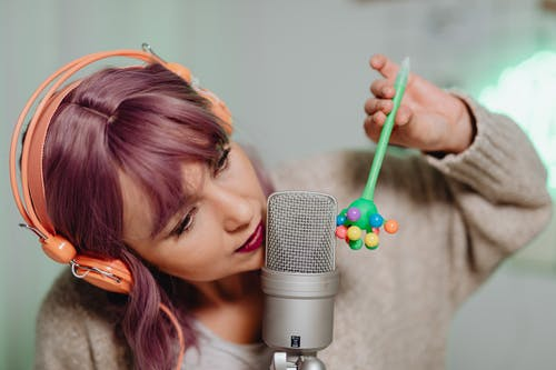 A Woman Recording on a Microphone