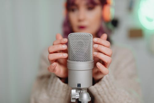 A Woman Touching a Microphone