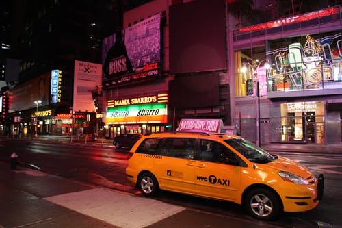 Yellow Hvc Taxi on Road during Night