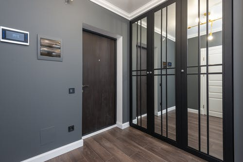 Interior of corridor of modern apartment with wooden doors and parquet floor and mirrored wardrobe