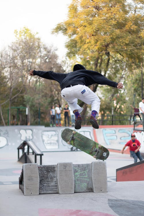 Man in Black Jacket and White Pants Jumping on Skateboard