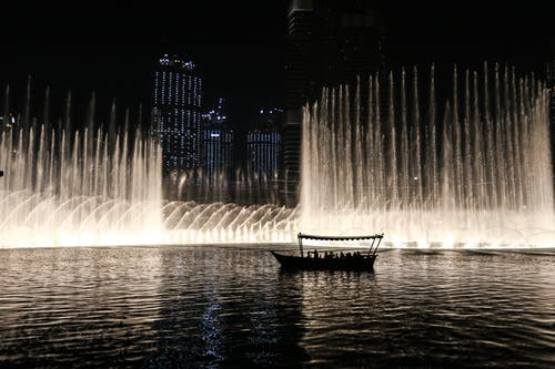 Silhouette of a Boat on a Body of Water With Fountain