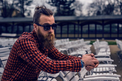 Man Wearing Black and Red Checkered Long Sleeve Shirt Wearing Black Wayfarer Sunglasses Sitting on White Wooden Chair