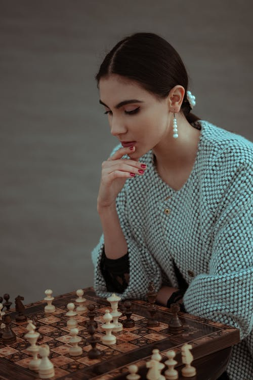 Focused woman thinking about next move and playing chess