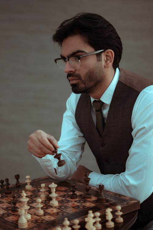 Contemplative bearded male in classy suit and eyeglasses playing chess during competition in studio