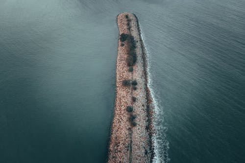 Drone view of rippling water of sea surrounding long stone breakwater in daytime