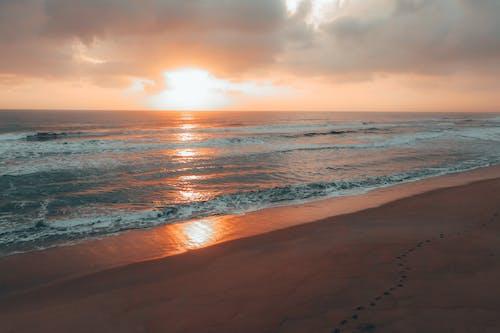 Foamy sea waving near sandy beach against cloudy sundown sky