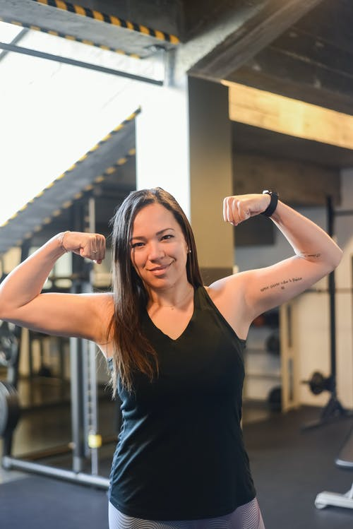 Confident Woman in Black Tank Top Flexing Her Biceps
