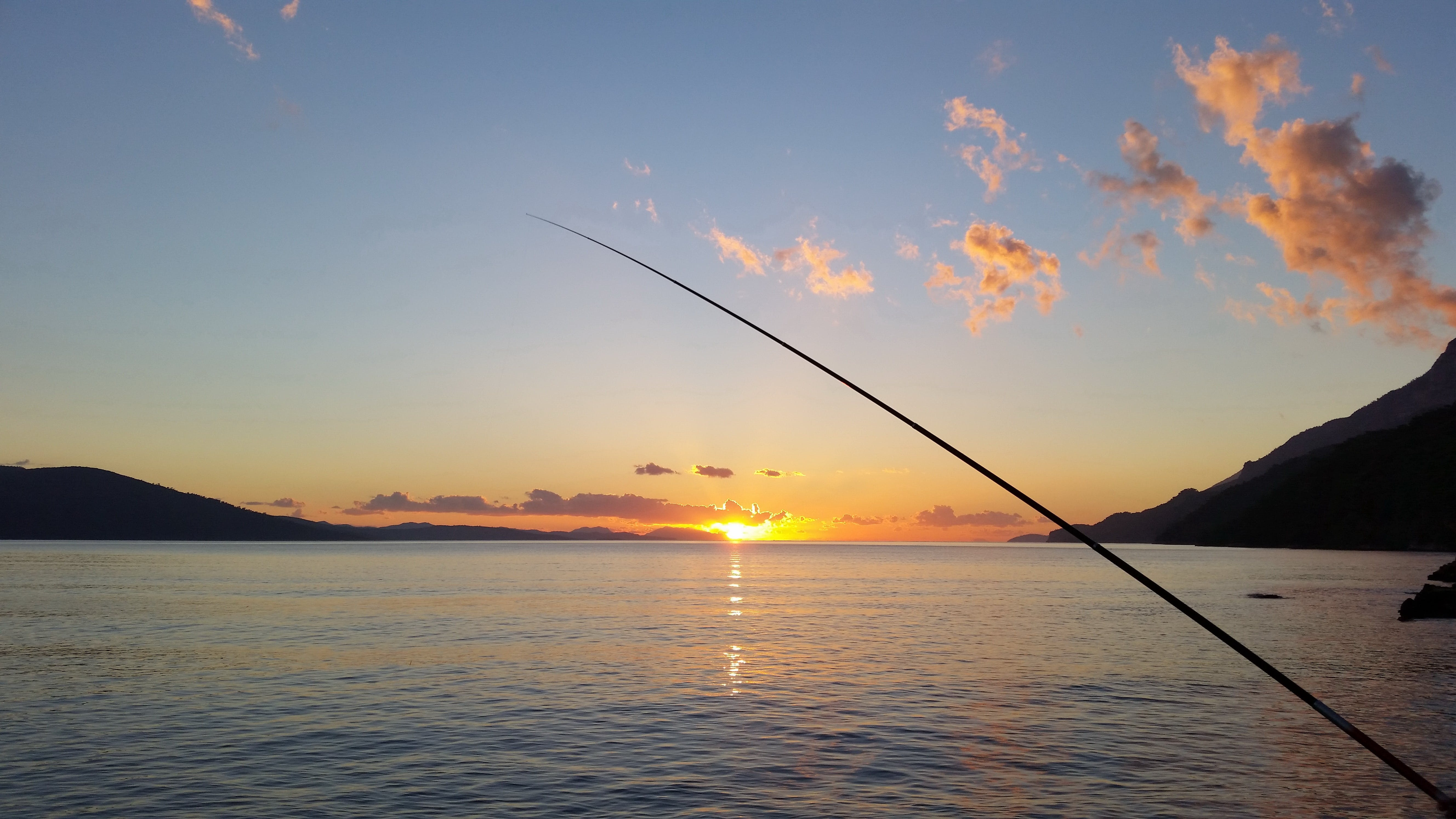Fishing Rod Near Body of Water during Sunset