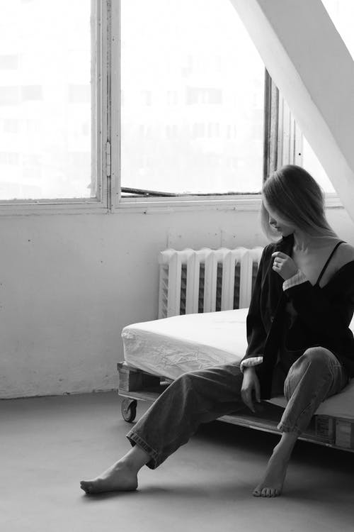 Black and white feminine female in unbuttoned shirt sitting on cozy bed near window