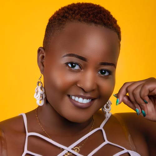 Smiling black woman with makeup and accessories in studio