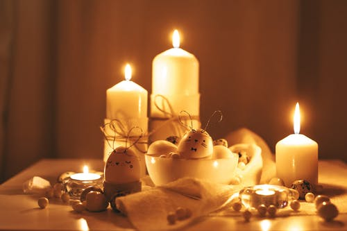 Lighted Candles And Painted Eggs On Golden Background