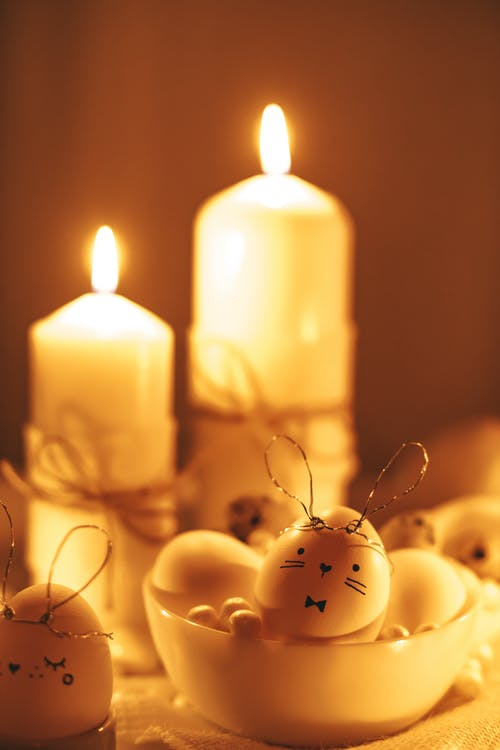 White Lighted Candles And Painted Eggs On Table