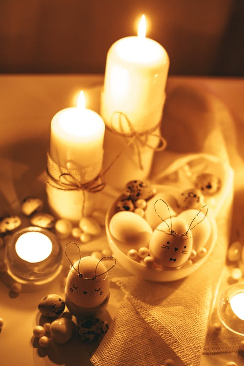 White Candles And Decorated Eggs on White Table