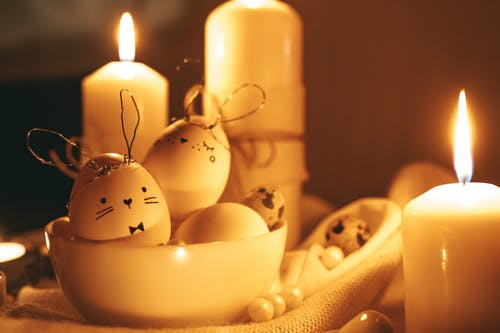 Lighted Candles And Painted Eggs With Golden Background