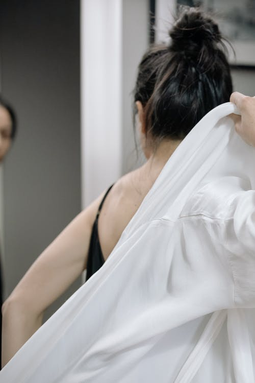 Woman in Black Tank Top Holding White Textile