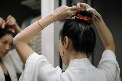 Woman in White Shirt Holding Her Hair