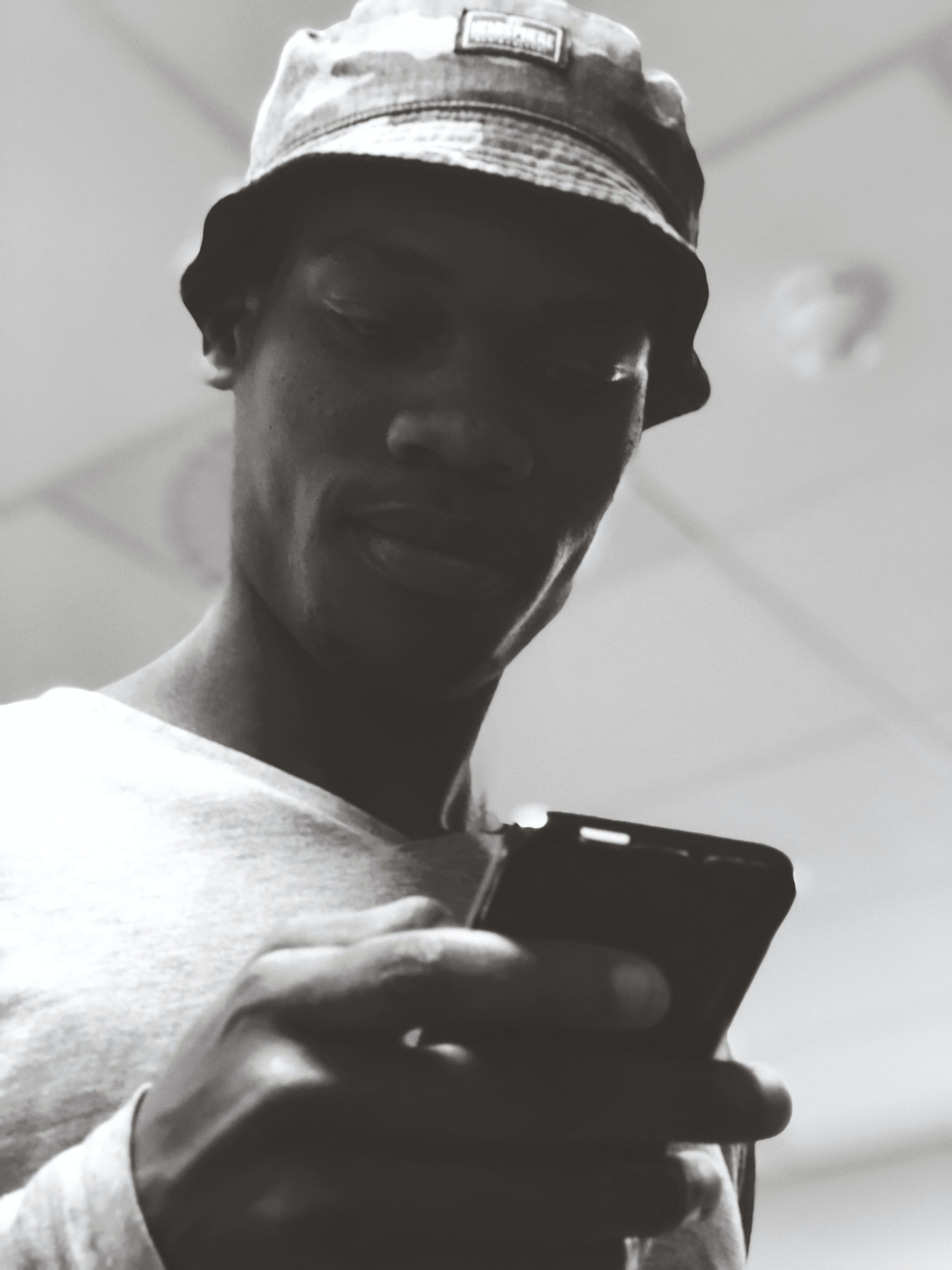 Man in Bucket Hat Holding Black Smartphone