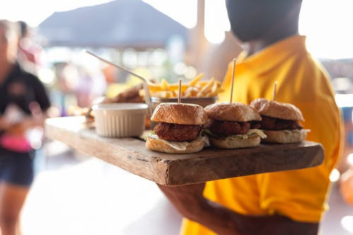 Close-Up Shot of a Person Holding a Wooden Tray with Burgers