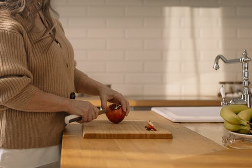 Woman Cutting  Pomegranate on Wooden Chopping Board