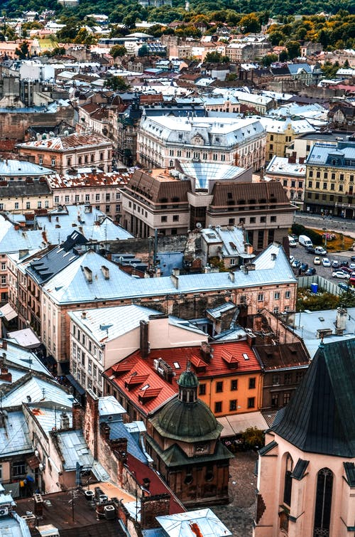 Picturesque drone view of Lviv cityscape with aged residential and historic buildings on sunny day