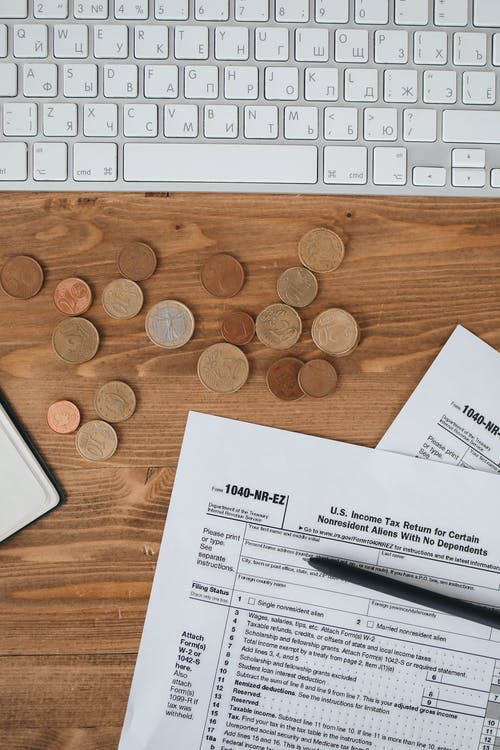 Income Tax Forms With Pen And Coins ON Wooden Surface
