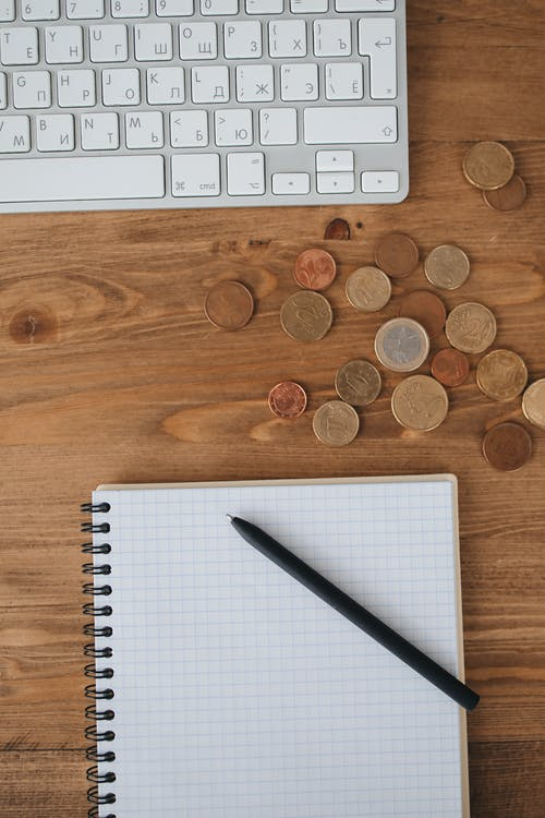Pen and Notebook Beside Some Coins and Keyboard