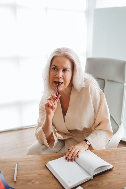 Woman Sitting by the Wooden Table While Thinking