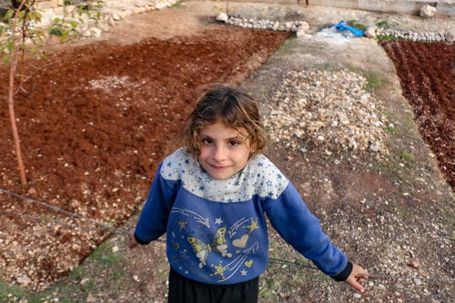 Cheerful ethnic child in sweatshirt ornament looking at camera on dry footpath in countryside