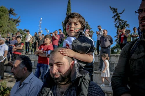 Smiling ethnic father with daughter on shoulders during strike