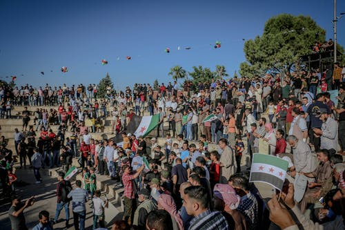 Crowd of anonymous Arab activists with Syrian flags on urban stairs during rally under blue sky
