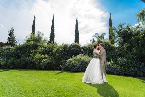 Woman in White Wedding Dress Standing on Green Grass Field Near Trees