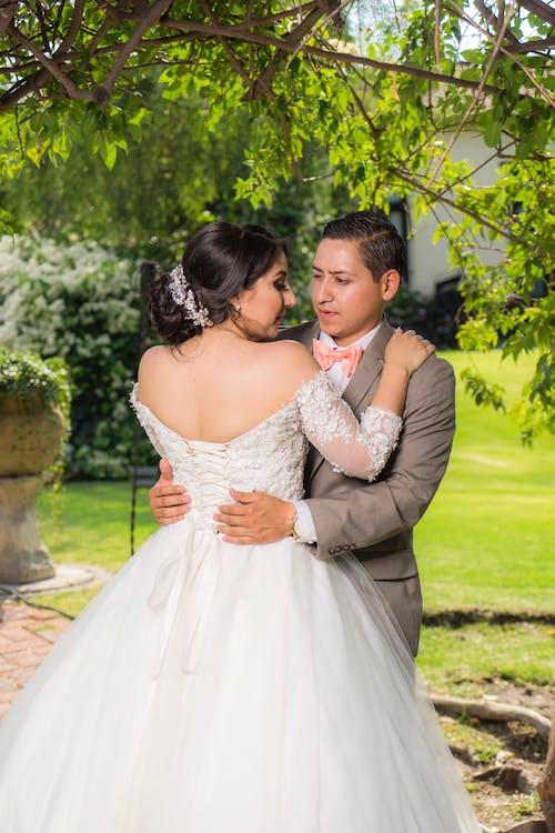 Man and Woman Kissing Near Green Grass