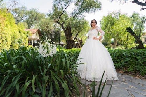 Woman in White Wedding Dress Standing Near Green Plants