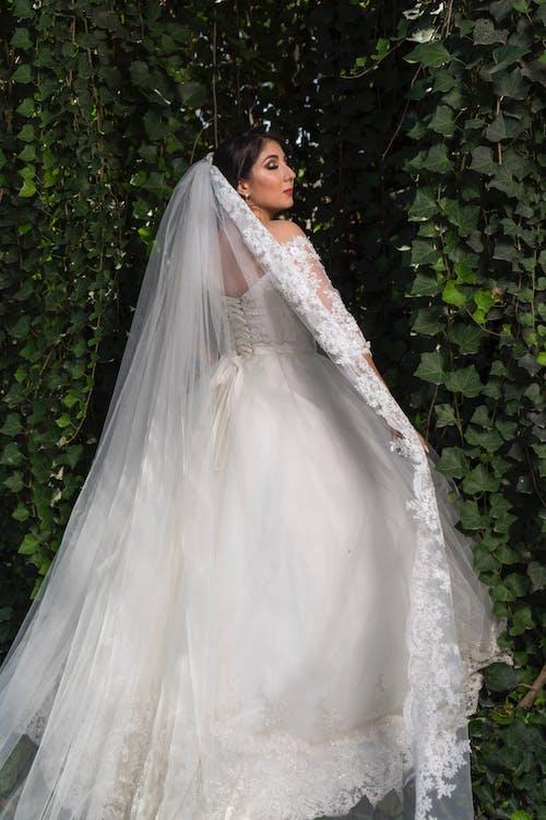Woman in White Wedding Dress Standing Beside Green Plants