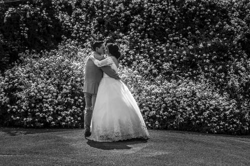 Grayscale Photo of Man and Woman Kissing