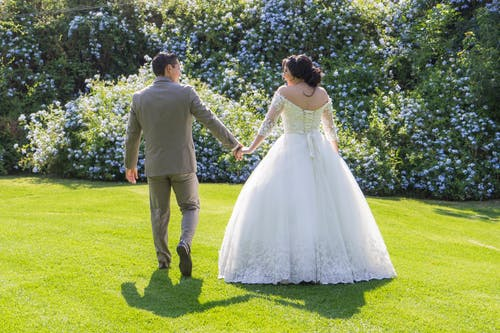 Man and Woman Holding Hands While Walking on Green Grass Field