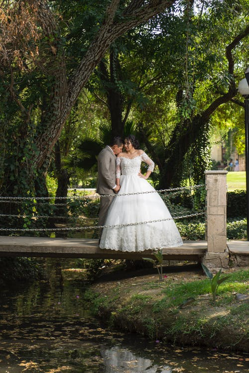 Man and Woman Kissing on Bridge Near Body of Water
