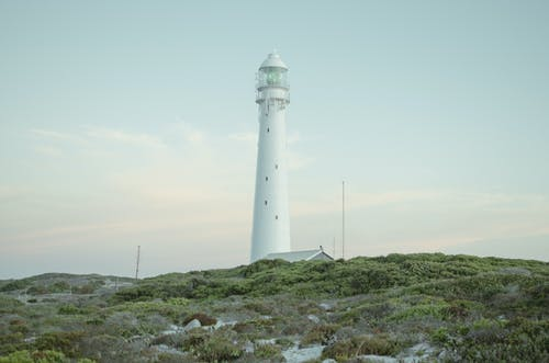 White Lighthouse on Green Grass Field Under White Sky