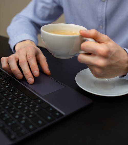 Crop anonymous male manager using touchpad while working on laptop and drinking aromatic cappuccino in morning office