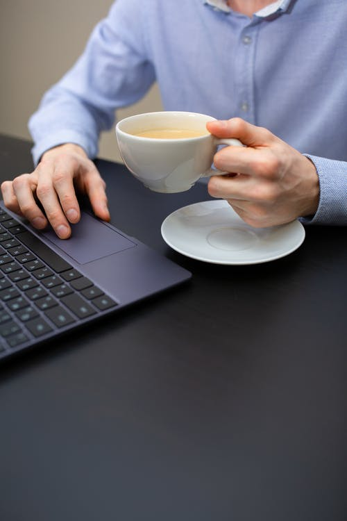 Crop male entrepreneur working on netbook and drinking cappuccino