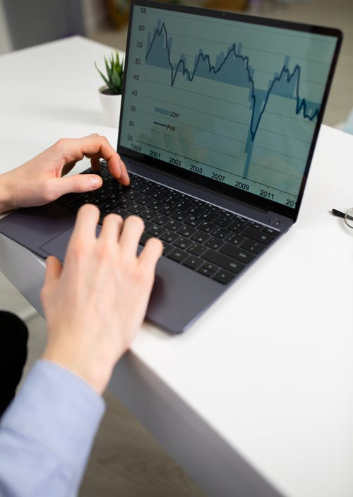Crop unrecognizable male entrepreneur typing on laptop keyboard while preparing financial diagrams during work in office
