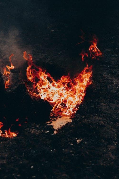 Bright flame on dark terrain under smoke in evening
