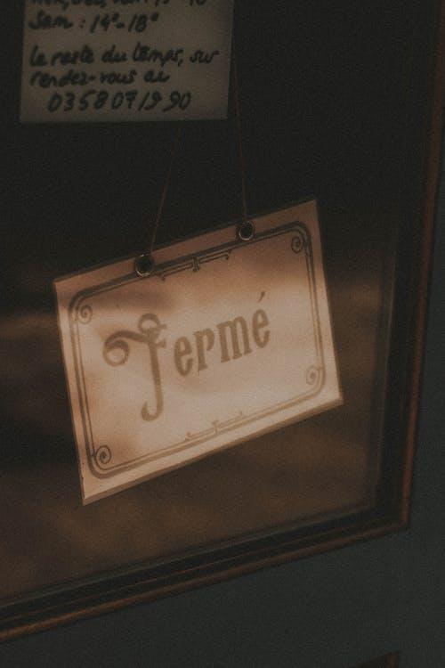 Retro signboard Ferme handing behind glass doors of shop in city street