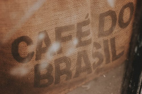 High angle closeup of burlap bag with coffee beans and inscription Cafe Do Brasil