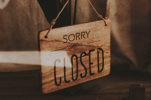Through glass of wooden signboard with inscription Sorry We Are Closed hanging on doors of shop
