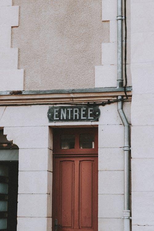 Sign Entree over door of building