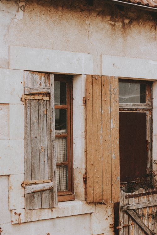 Old wooden shutters on windows of shabby residential house with wrecked walls in countryside